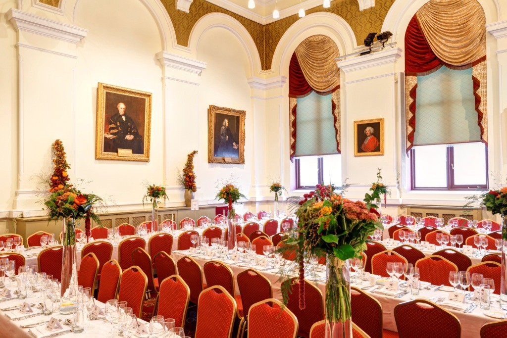 Number 6 Kildare St. Dublin Corrigan Hall set for large dinner event with flower arrangements in tall glass vases