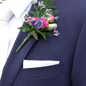 Boutonnaire of roses and lisianthus for gents suit at wedding