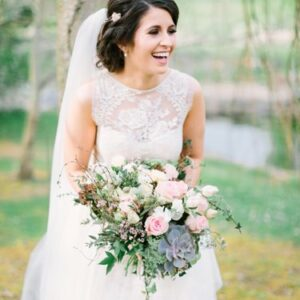 bride with her bridal bouquet made with roses succulents ivy and lisianthus