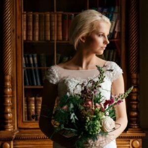 Pensive bride with a wild and natural style wedding flower bouquet.