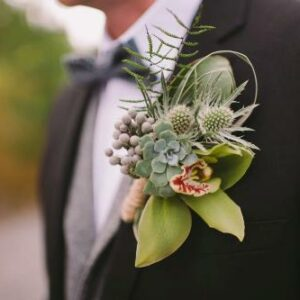 Grooms wedding buttonhole flowers of orchid and thistle