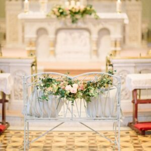 Floral decoration for chairs at wedding service