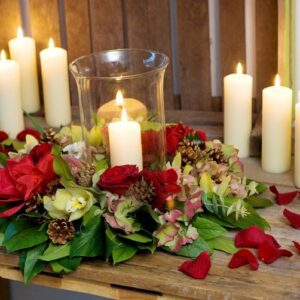 Table centre of hurricane lamp with flowers for a Christmas event