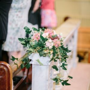 Church pew end decorated with wedding flowers