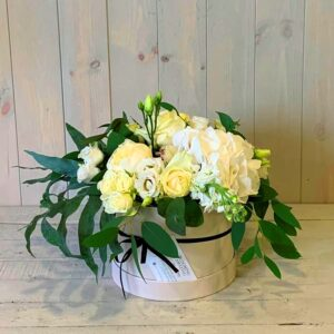 Pretty hatbox flower arrangement in creams, greens and white shades.