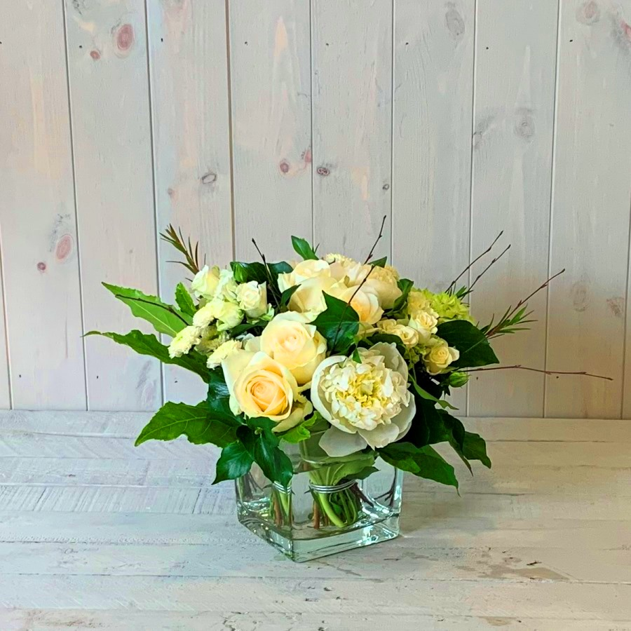 flower arrangement in creams greens and whites in glass cube vase.Creams