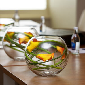 Flower arrangements set in fishbowls to decorate a meeting room