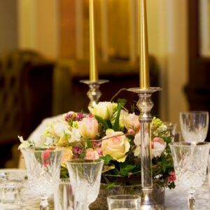 Table centre of wedding flowers in Dublin hotel with gold candles