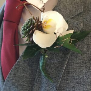 Grooms buttonhole made of orchid and pine cone from our wedding flower costs page