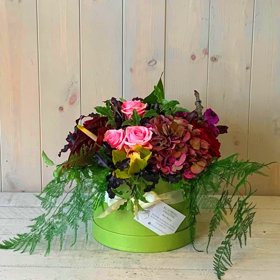 flowers in pinks and reds set in a pretty hatbox. Flower delivery available in Dublin