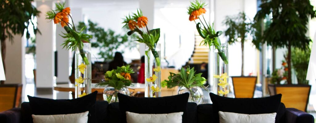 Flowers for hotels restaurants and venues - Hotel lobby with three part tall flower arrangementwith trio