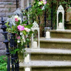 Church stairs decorated with flowers and huricane lanterns