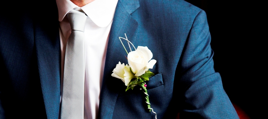 Groom wearing buttonhole of white avalance roses from our guide to wedding costs