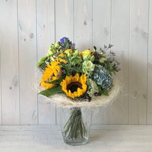A sunny summer flower bouquet of sunflowers set in a sisal frame. Ready for delivery in Dublin Ireland.