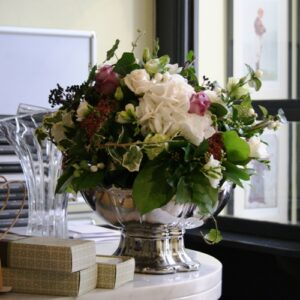 wedding flower pictures - table arrangement of white hydrangea with pink and purple seasonal flowers in a silver vase.