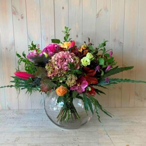 Flower bouquet in pinks in goldfish bowl vase