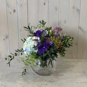 A blue summer themed flower bouquet set in a goldfish bowl vase for delivery in Dublin